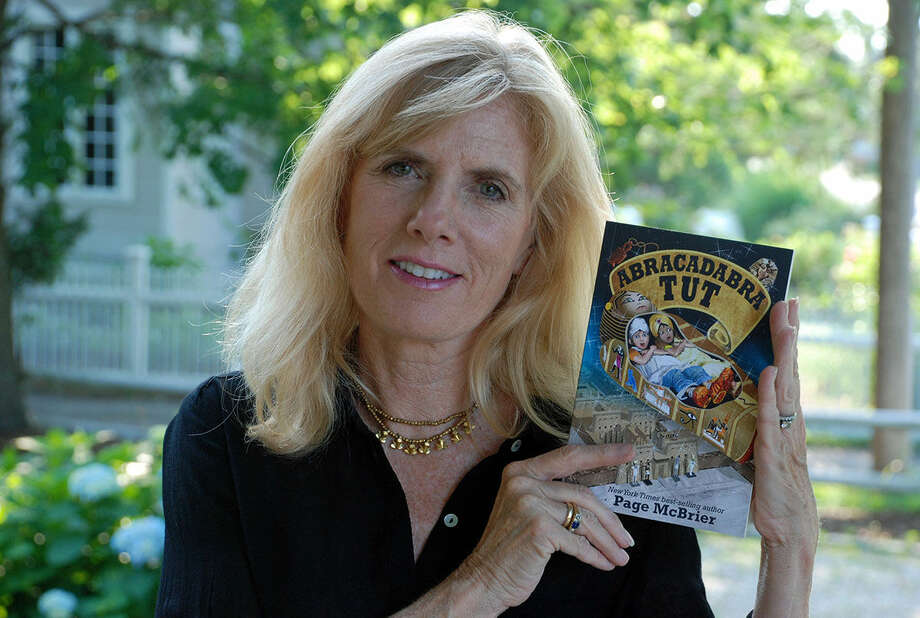 """Contributed photo Page McBrier holds up a copy of her children's book """"Abracadabra Tut."""""""