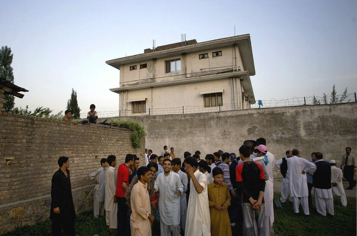FILE - In this May 3, 2011 file photo, local residents gather outside a house, where al-Qaida leader Osama bin Laden was caught and killed in Abbottabad, Pakistan. After U.S. Navy SEALs killed Osama bin laden in Pakistan in May 2011, top CIA officials secretly told lawmakers that information gleaned from brutal interrogations played a key role in what was one of the spy agency's greatest successes. CIA director Leon Panetta repeated that assertion in public, and it found its way into a critically acclaimed movie about the operation, Zero Dark Thirty, which depicts a detainee offering up the identity of bin Laden's courier, Abu Ahmad al- Kuwaiti, after being tortured at a CIA