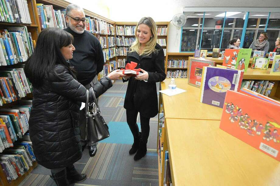 Hour Photo/Alex von Kleydorff SONO Ice House General manager Dale DeRosa presents librarian Joanna Cimoch with some books about hockey at the Silvermine School's new Learniing Commons