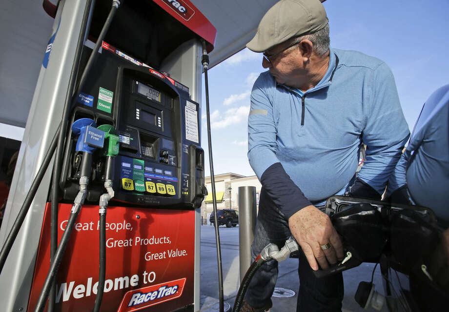 Eduardo Palacios-Paez, of Miami, pumps gas at a RaceTrac gasoline station, Friday, Dec. 12, 2014, in Hialeah, Fla. Motorists are now seeing prices under $3 a gallon for the first time in four years, which also means that gas stations are paying less for the fuel, too. (AP Photo/Wilfredo Lee)