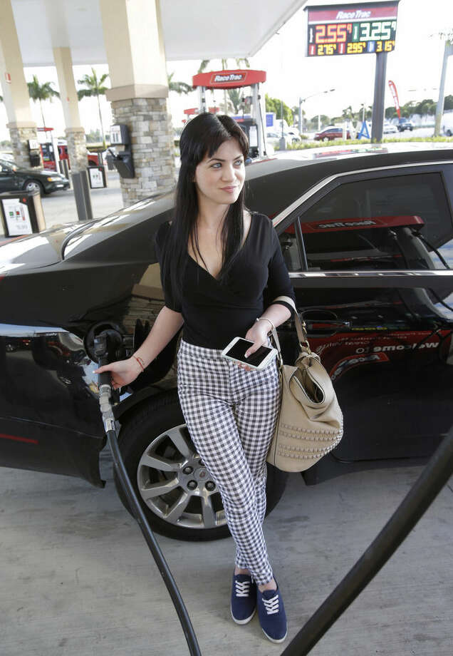 In this Thursday, Dec. 11, 2014 photo, Chanel Acosta, of Hialeah, Fla., pumps gas into her car at a RaceTrac gasoline station in Hialeah. Motorists are now seeing prices under $3 a gallon for the first time in four years, which also means that gas stations are paying less for the fuel, too. (AP Photo/Wilfredo Lee)