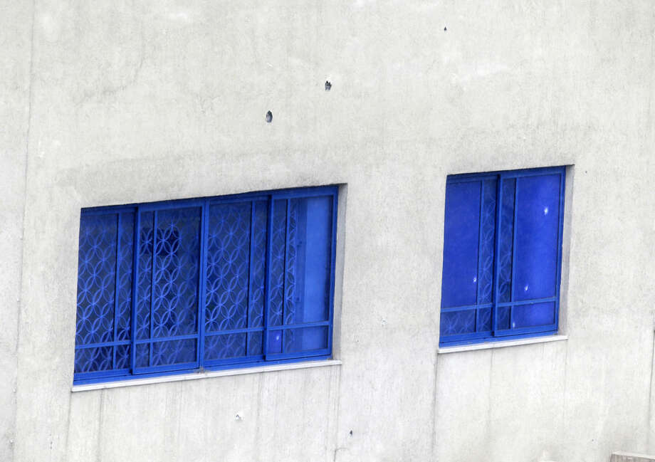 Bullet holes are seen on the wall of Israeli Embassy after a pre-dawn gunfire attack in Athens, Friday, Dec. 12, 2014. Greek authorities are investigating the pre-dawn, drive-by gunfire attack on the Israeli embassy and officials said at least 20 bullet casings were found near the scene of the attack, which occurred long before the building opened for business. (AP Photo/Thanassis Stavrakis)