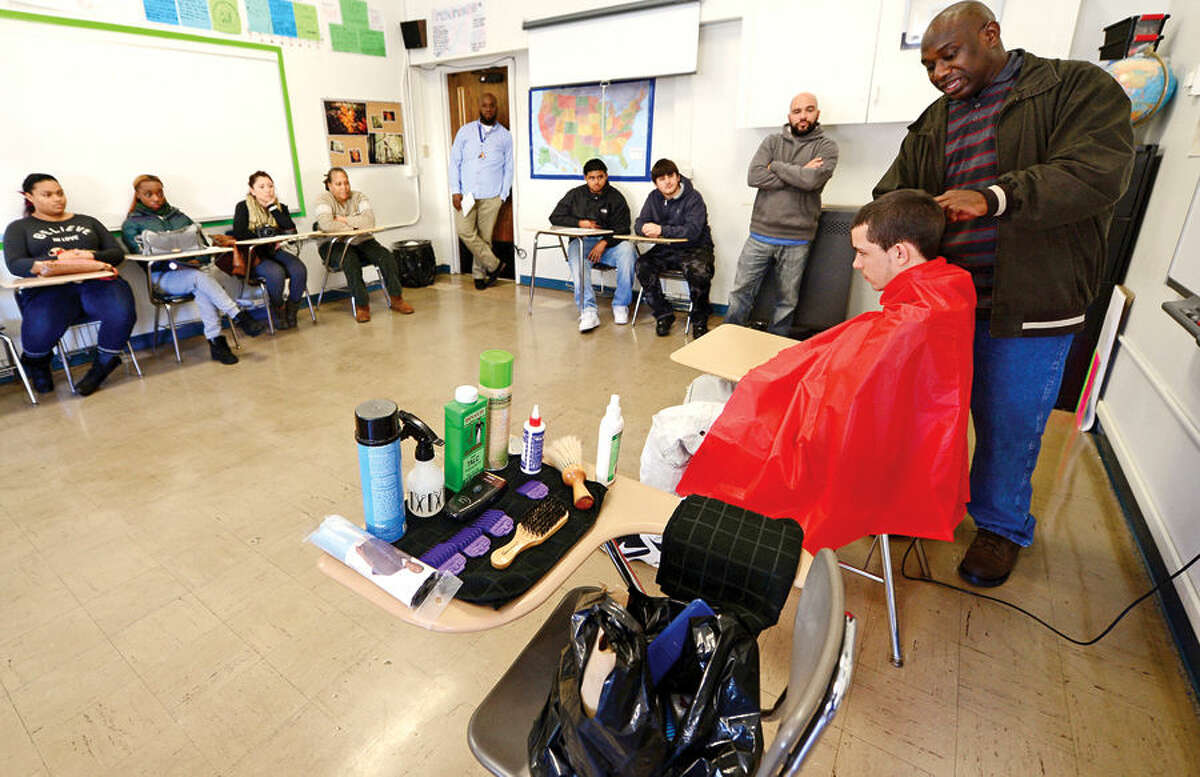 Hour photo / Erik Trautmann Briggs High School students watch as Hair Tech owner Vincent Grant cuts the hair of student Alex Cardone during the school's weekly Friday Academy where local trades people introduce students to their career.