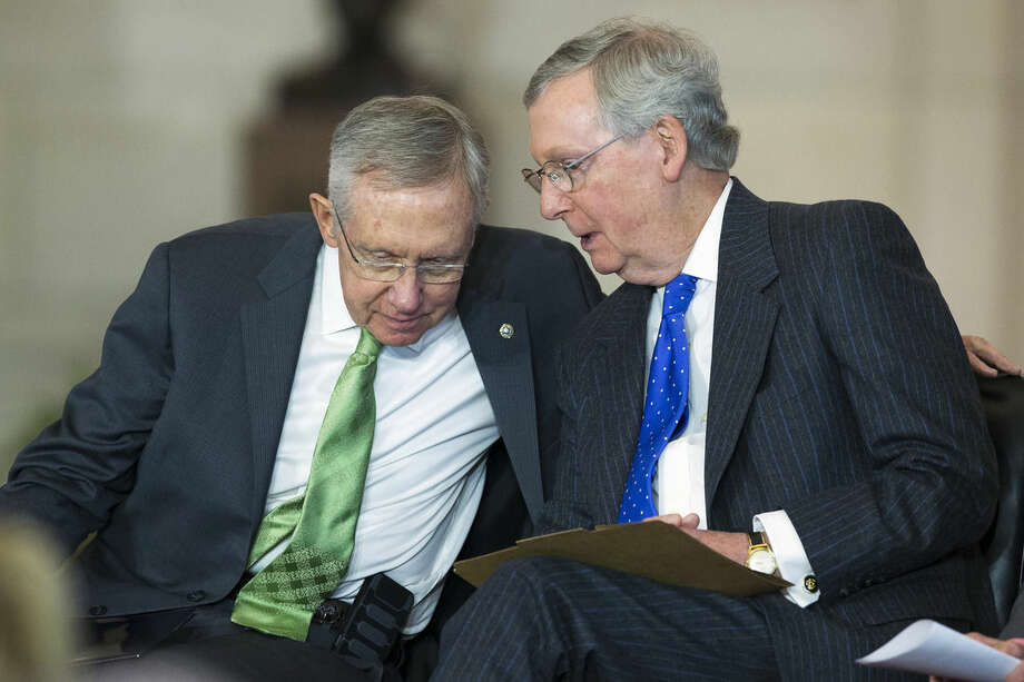 Senate Majority Leader Sen. Harry Reid of Nev., left, talks with Senate Minority Leader Sen. Mitch McConnell of Ky. on Capitol Hill in Washington, Wednesday, Dec. 10, 2014, during a ceremony to present the Congressional Gold Medal to members of the Civil Air Patrol whose valor and dedication saved countless lives during World War II. (AP Photo/Evan Vucci)