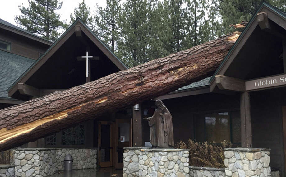 In this photo provided by the Tahoe Douglas Fire Protection District, a toppled tree nearly hits a prominent statue in front of the Saint Theresa Catholic Church in South Lake Tahoe, Calif. on Thursday, Dec. 11, 2014. High winds ahead of a powerful Pacific storm swept through South Lake Tahoe. Tahoe Douglas Fire Protection District Fire Marshal Eric Guevin said the church was damaged, but no one was injured. (AP Photo/Tahoe Douglas Fire Protection District, Capt. Chris Lucas)