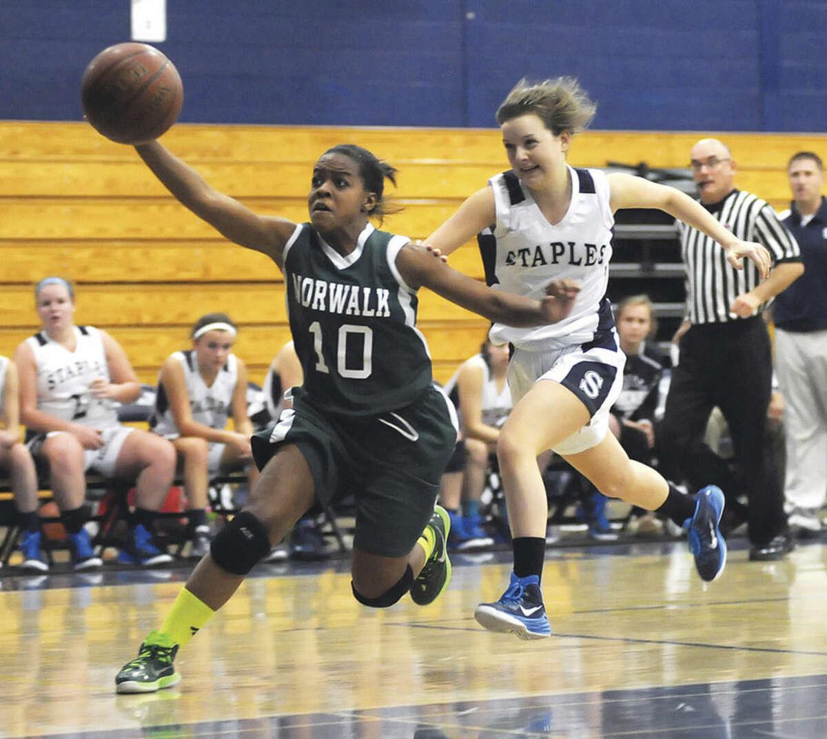 Hour photo/John Nash Norwalk's Jackie Harris, left, tracks down a ball in front of Staples' Rachel Seideman during Wednesday's season-opening FCIAC girls basketball game in Westport. Staples won, 43-38.