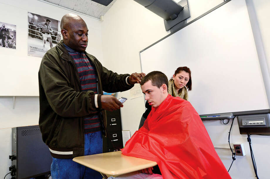 Hour photo / Erik Trautmann Briggs High School students including Marcela Menjiuan watch as Hair Tech owner Vincent Grant cuts the hair of Alex Cardone during the school's weekly Friday Academy where local trades people introduce students to their career.