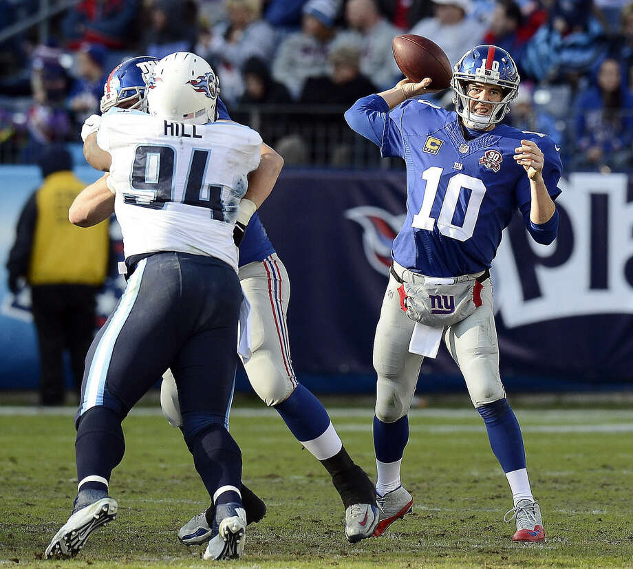 New York Giants quarterback Eli Manning (10) passes as Tennessee Titans nose tackle Sammie Lee Hill (94) rushes in the second half of an NFL football game Sunday, Dec. 7, 2014, in Nashville, Tenn. (AP Photo/Mark Zaleski)