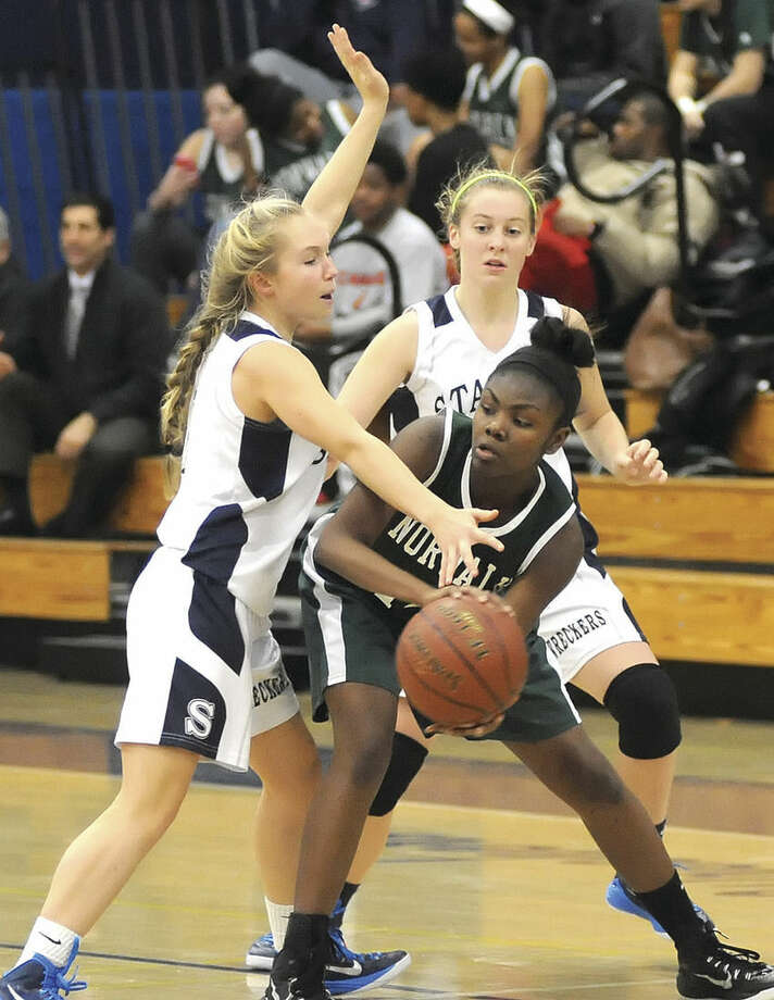 Hour photo/John NashNorwalk's Asiah Knight, center, is trapped by Staples' Olivia Troy, left, and Tessa Mall, rear, during Wednesday's season-opening FCIAC girls basketball game in Westport. Staples won, 43-38.
