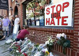 NEW YORK, NY - JUNE 12: Nicolas Brown-Spino, 6, sets down a paper flower at a make-shift memorial in front of the Stonewall Inn as people gather for a vigil following the massacre that occurred at a Orlando nightclub on June 12, 2016 in New York City. A gunman who allegedly pledged allegiance with ISIS opened fired in the gay nightclub in Florida killing over 50 people.  (Photo by Monika Graff/Getty Images)