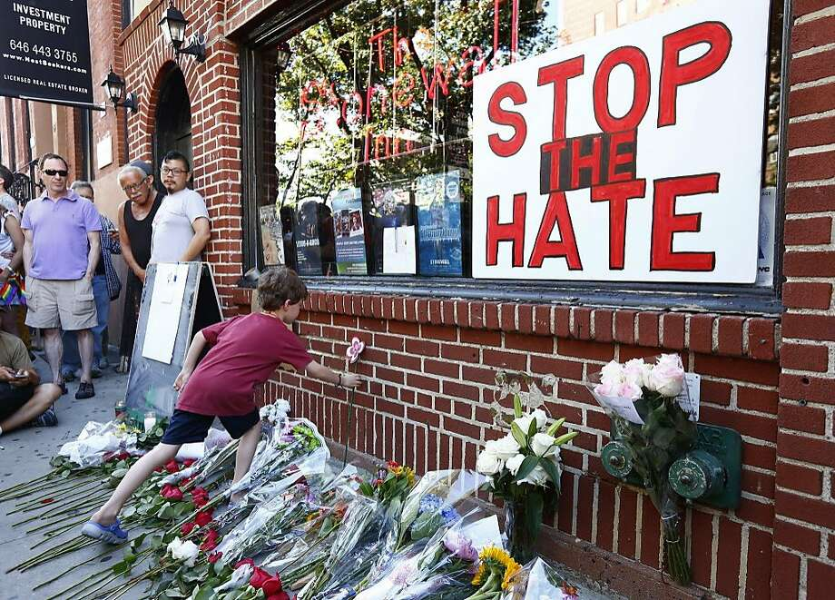 NEW YORK, NY - JUNE 12: Nicolas Brown-Spino, 6, sets down a paper flower at a make-shift memorial in front of the Stonewall Inn as people gather for a vigil following the massacre that occurred at a Orlando nightclub on June 12, 2016 in New York City. A gunman who allegedly pledged allegiance with ISIS opened fired in the gay nightclub in Florida killing over 50 people.  (Photo by Monika Graff/Getty Images) Photo: Monika Graff, Getty Images