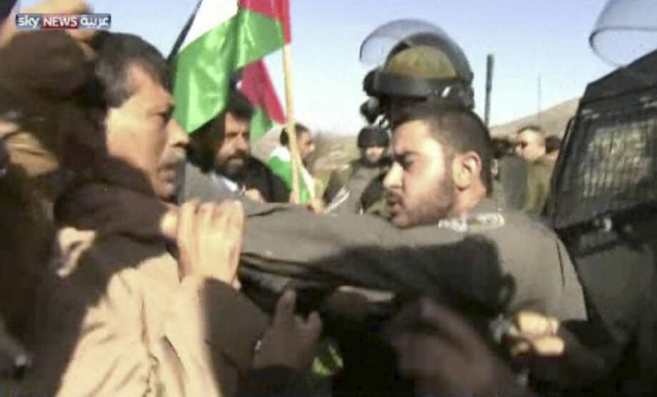 """In this image taken from video, an Israeli officer, right, grabs the throat of Palestinian Cabinet member Ziad Abu Ain during a protest in the West Bank city of Turmus Aya, Wednesday, Dec. 10, 2014. Abu Ain died Wednesday following the scuffle with Israeli troops, quickly stirring Palestinian anger at a time of badly strained relations with Israel. An autopsy has yet to determine what killed Abu Ain, but Palestinian President Mahmoud Abbas called him the victim of a """"clear crime"""" and a """"barbaric act."""" He decreed three days of mourning for the minister, whose portfolio included organizing protests against Israeli settlements and the West Bank separation barrier. (AP Photo/Sky News Arabia via AP Video)"""