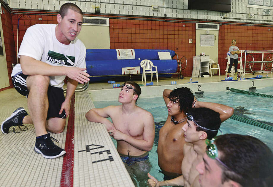 Hour photo/Erik TrautmannNew Norwalk/McMaohn boys swimming coach Chris Passamano, left, talks with his swimmers Tuesday afternoon.