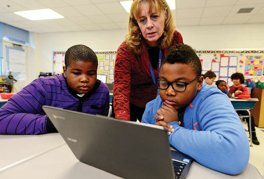 Hour photo / Erik Trautmann Kendall Elementary School 4th grade teacher Rose Bernheim helps her students, Jeanel Pierre and Josh Dupree Thursday with their Hour of Code lesson, a worldwide initiative to teach students coding and computer programming.