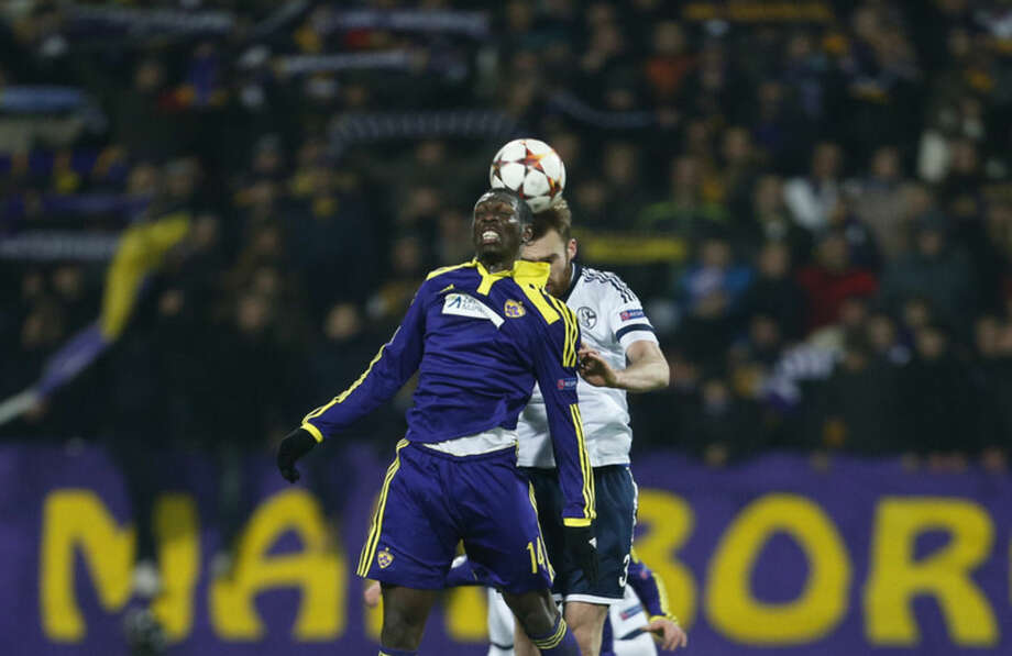 Maribor's Jean-Philippe Mendy, left, jumps for a header with Schalke's Jan Kirchhoff during the Champions League group G soccer match between Maribor and Schalke 04, at Ljudski Vrt stadium, in Maribor, Slovenia, Wednesday, Dec. 10, 2014.(AP Photo/Darko Bandic)