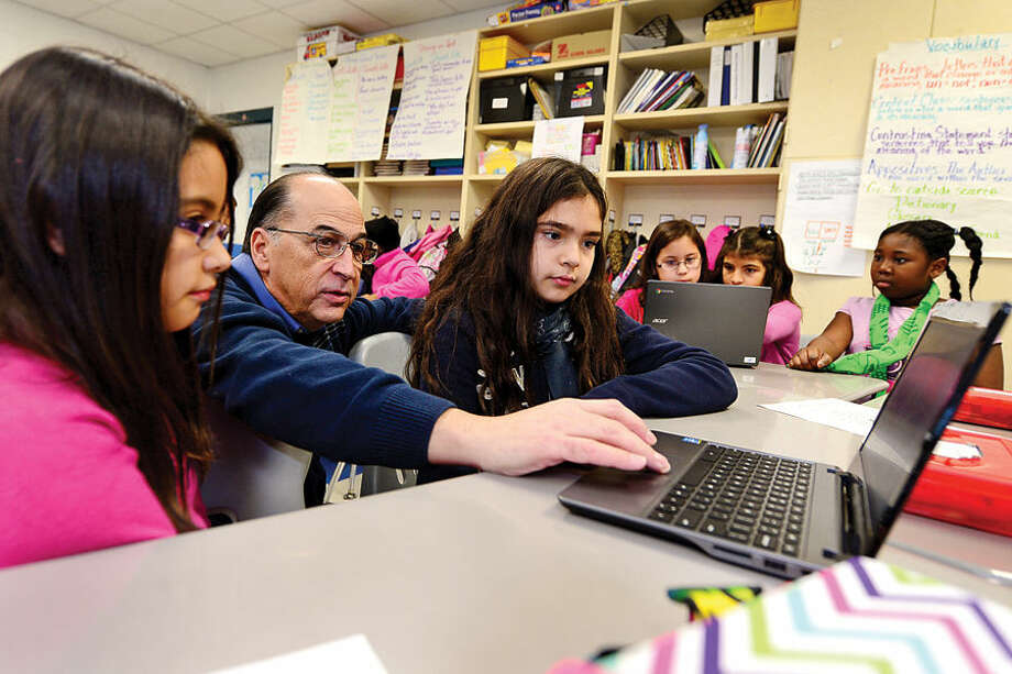 Hour photo / Erik Trautmann Kendall Elementary School principal helps 4th graders Jazmine Sosa and Olivia Araujo Thursday with their Hour of Code, a worldwide initiative to teach students coding and computer programming.
