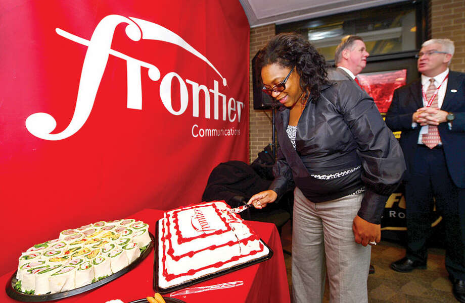 Hour photo / Erik Trautmann Frontier's VP of Marketing for the East Region cuts the cake in celebration of their new retail location in Norwalk Thursday. Frontier's new store will offer customers a fully staffed, expansive center for learning about and ordering the company's comprehensive internet and televison and phone products and services.