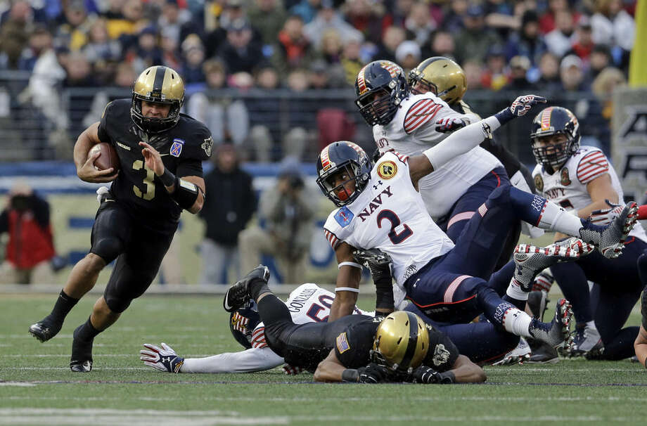 Army quarterback Angel Santiago, left, rushes past Navy defenders for a first down in the first half of the Army-Navy NCAA college football game, Saturday, Dec. 13, 2014, in Baltimore. (AP Photo/Patrick Semansky)