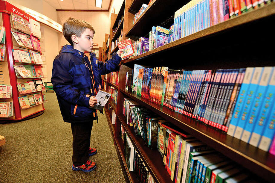 Hour photo / Erik Trautmann Anthony Szarpa shops for a new book in the Genimo Stilton series during the Barnes & Noble and The Norwalk Public Library World of Books book fair Saturday. The book fair continues on Sunday, December 14h and will support Library Programming by donating a percentage of qualifying purchases to The Norwalk Public Library.