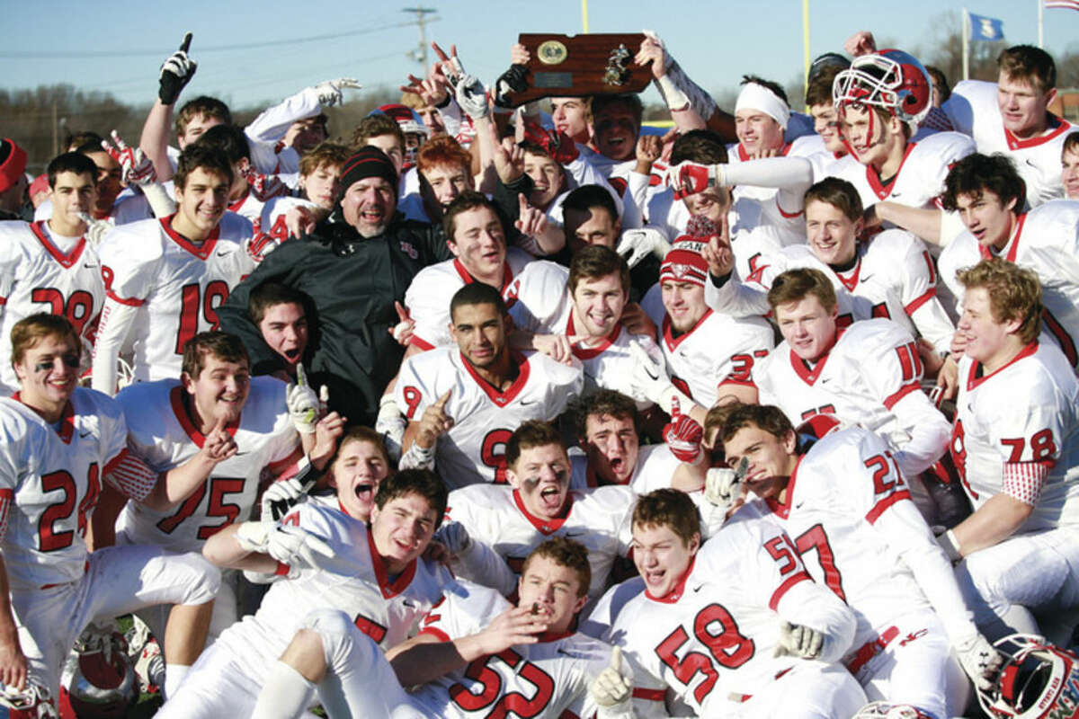 Hour photo/Chris Palermo New Canaan celebrates with the state championship trophy after their 21-20 victory over Darien at Ken Strong Stadium in West Haven Saturday.