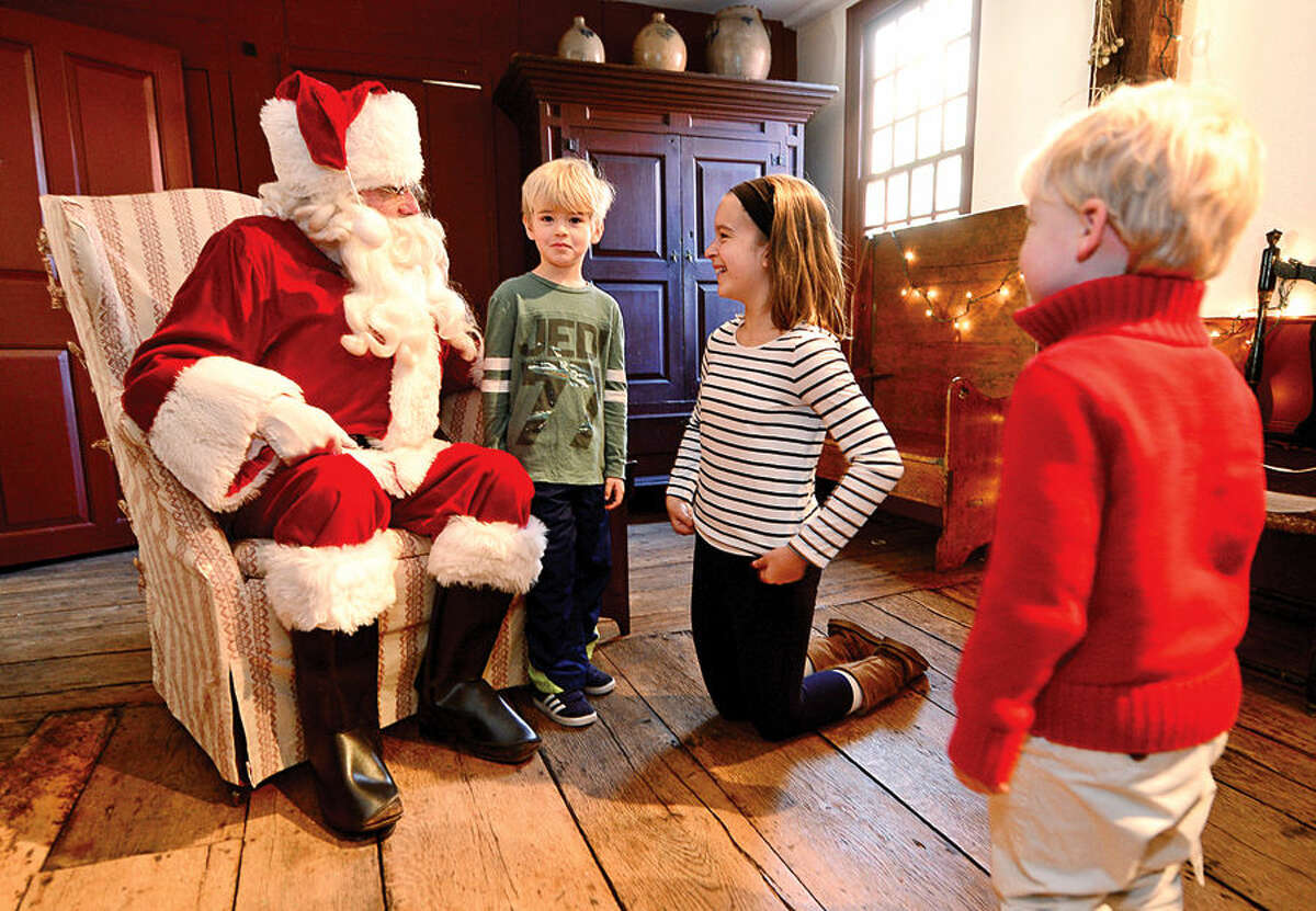 Hour photo / Erik Trautmann Colby Fowler, 6, tells Santa, aka Mark Dolnier, what he wants for Christmas as his sister Morgan Fowler, 11, and Brady Fowler, 3, look on during The Wilton Historical Society's Holiday Train Exhibit Saturday.