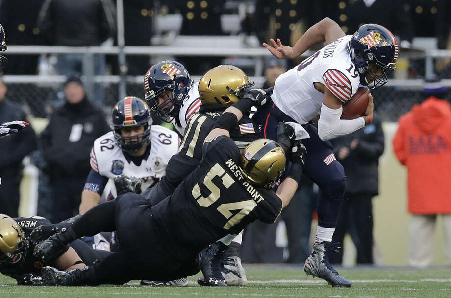 Navy quarterback Keenan Reynolds, right, is tackled for a loss of yards by Army defensive lineman Joe Drummond (54) and linebacker Andrew King in the first half of an NCAA college football game, Saturday, Dec. 13, 2014, in Baltimore. (AP Photo/Patrick Semansky)