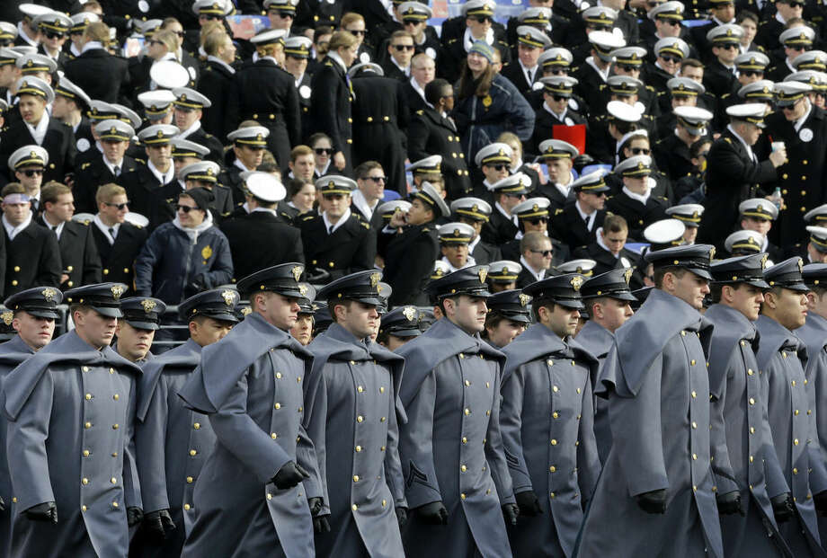 Army Cadets, bottom, march past Navy Midshipmen in the stands before the Army-Navy NCAA college football game, Saturday, Dec. 13, 2014, in Baltimore. (AP Photo/Patrick Semansky)