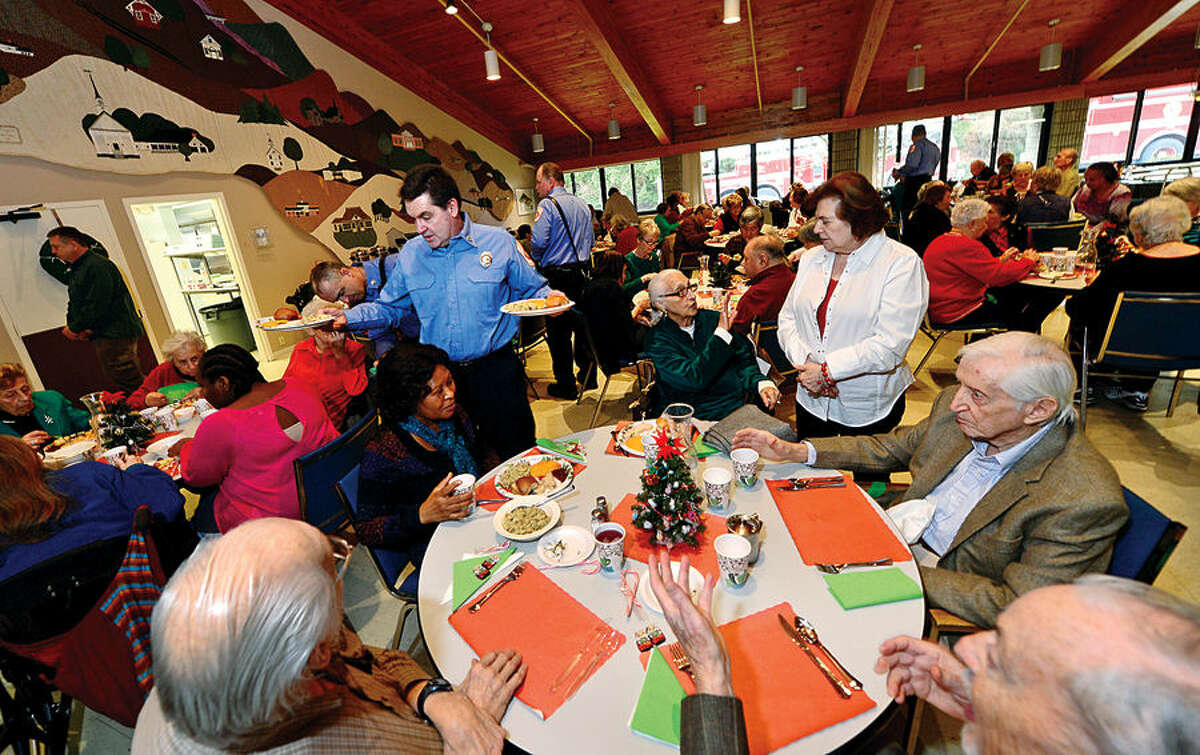Hour photo / Erik Trautmann Ogden House residents enjoy their annual Christmas turkey dinner served by Wilton Career Firefighters Wednesday.