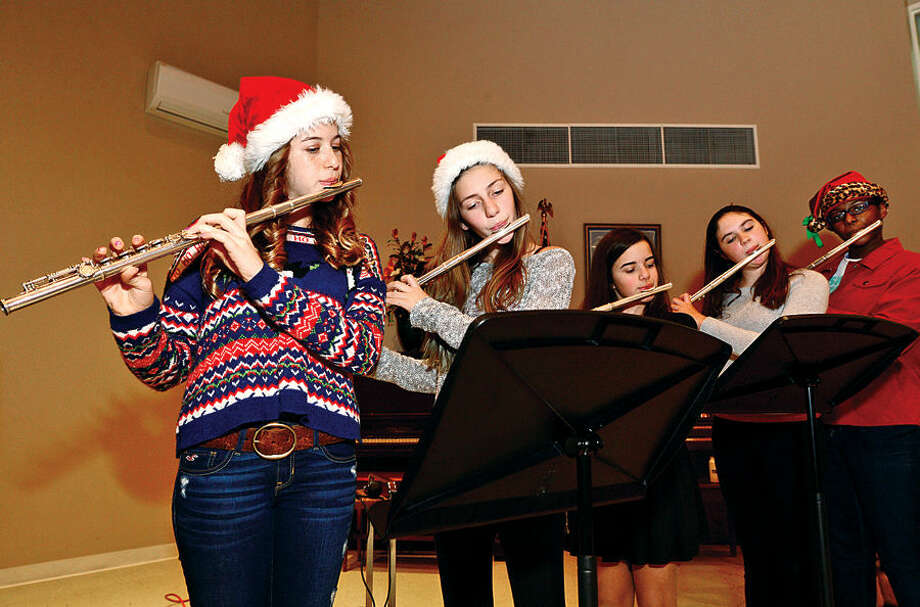 Hour photo / Erik Trautmann Middlebrook Middle School flutists Natalie Wallon, Caitlin Hearl, Katie Pruden, Devon Dooley and Sydney Cummings play for Ogden House residents as they enjoy their annual Christmas turkey dinner served by Wilton Career Firefighters Wednesday.