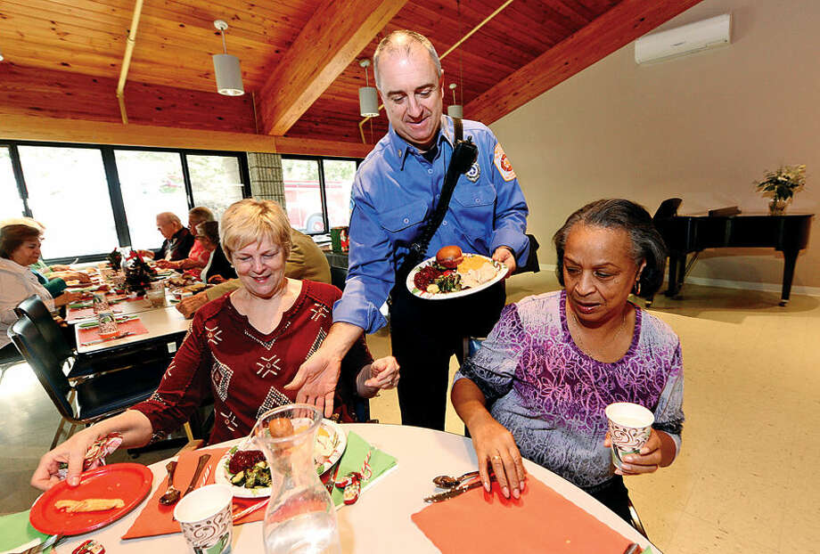Hour photo / Erik Trautmann Ogden House residents enjoy their annual Christmas turkey dinner served by Wilton Career Firefighters including firefighter Patrick Garber Wednesday.