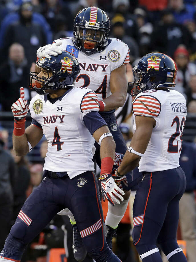 Navy wide receiver Jamir Tillman (4) celebrates his touchdown with teammates Ryan Williams-Jenkins (24) and Geoffrey Whiteside in the first half of an NCAA college football game against Army, Saturday, Dec. 13, 2014, in Baltimore. (AP Photo/Patrick Semansky)