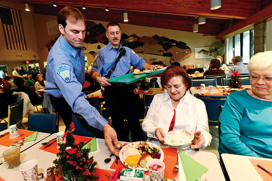 Hour photo / Erik Trautmann Ogden House residents Donna Ruddy and Phyllis Boroskey enjoy their annual Christmas turkey dinner served by firefighters Glenn Johnson and Gary Fuoco and the Wilton Career Firefighters Wednesday.