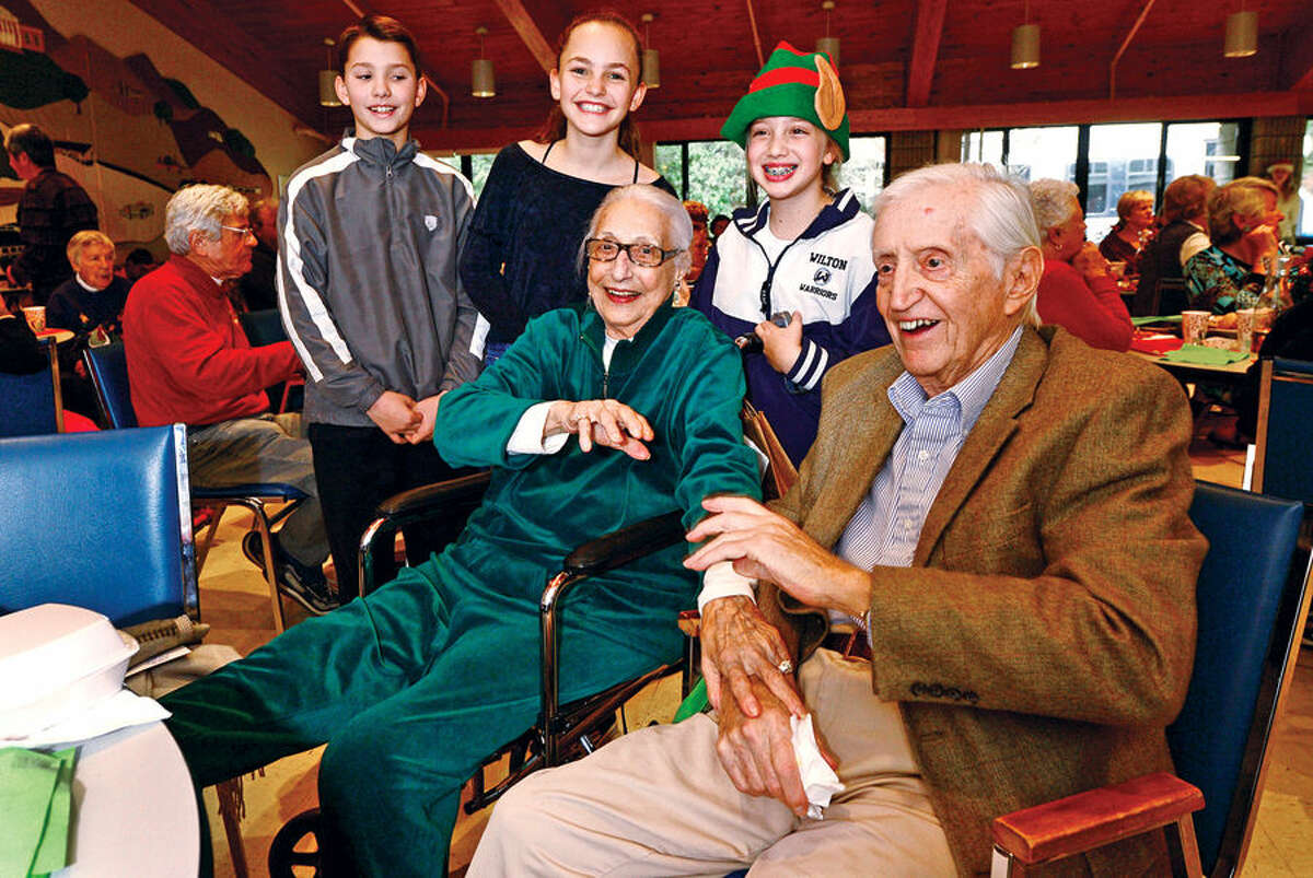 Hour photo / Erik Trautmann Ogden House residents Lee Sprei and Tom Swik pose for photos with Middlebrook Middle School student council members Josh White, Eleanor Greene and Jordan Smith enjoy their annual Christmas turkey dinner served by firefighters Glenn Johnson and Gary Fuoco and the Wilton Career Firefighters Wednesday.