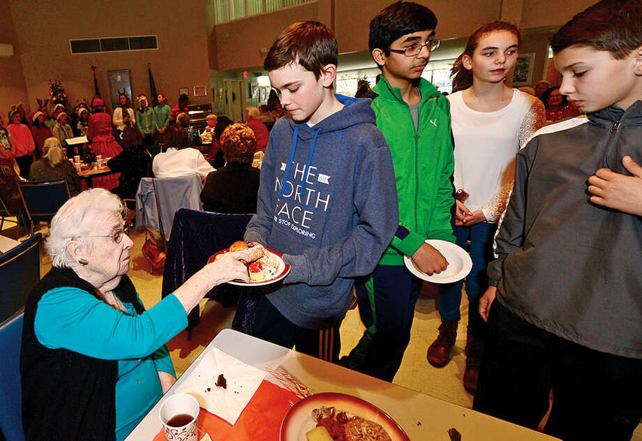 Hour photo / Erik Trautmann Ogden House residents including Catherine Gallery enjoy their annual Christmas turkey dinner desert served by Middlebrook Middle School student council members Davis Langhoff, Rishabh Raniwala, Anna Thorton and Josh White Wednesday.