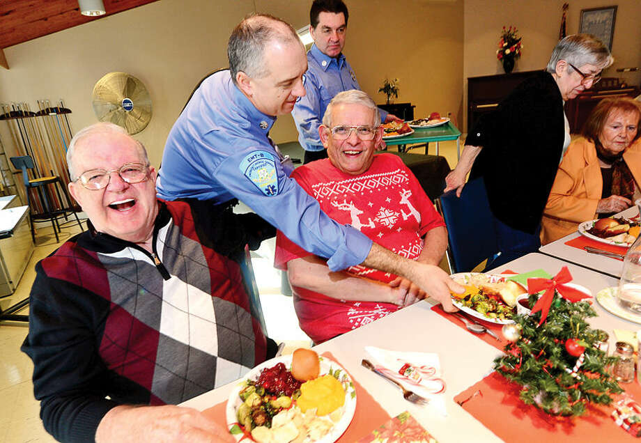 Hour photo / Erik Trautmann Ogden House residents including Paul Scluntz and John Vetrano enjoy their annual Christmas turkey dinner served by Firefighters Patrick Garber and Kevin Plank and the Wilton Career Firefighters Wednesday.