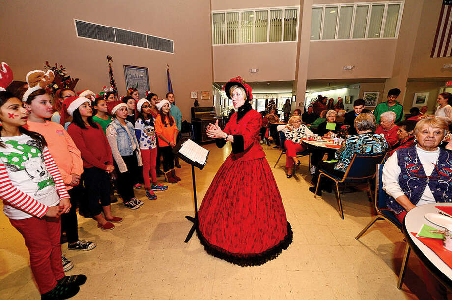 Hour photo / Erik Trautmann The Middlebrook Singers led by co-director Susan Kelly Ogden House residents enjoy their annual Christmas turkey dinner served by Wilton Career Firefighters Wednesday.