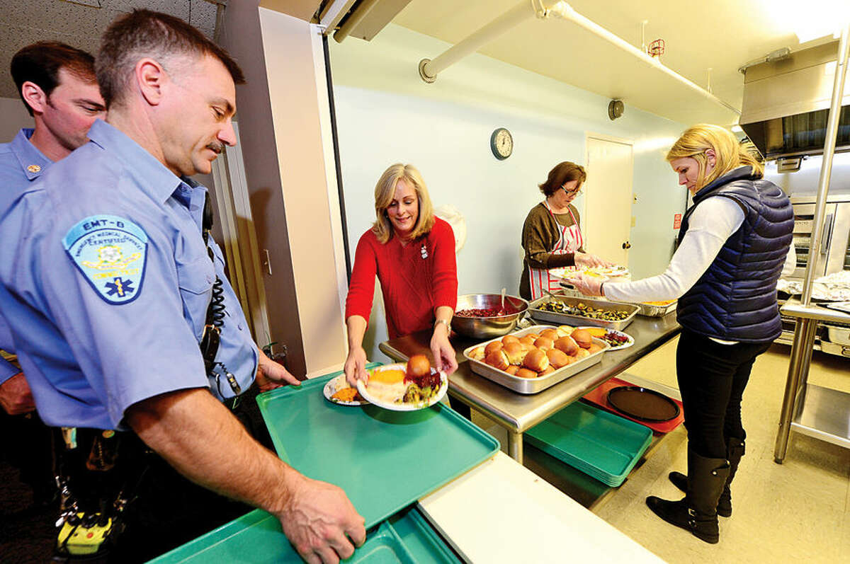 Hour photo / Erik Trautmann Wilton Women's Club members Marcia Gillespie, Mary Belgen and Tina Donovan prepare the annual Christmas turkey dinner for Ogden House residents served by Firefighter gary Fuoco and Wilton Career Firefighters Wednesday.