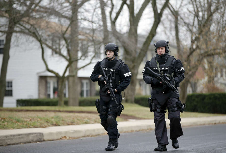 Police search for suspect Bradley William Stone, Tuesday, Dec. 16, 2014, in Pennsburg, Pa. Schools closed and hospitals and other public places tightened security Tuesday, as police in suburban Philadelphia hunted for the Marine veteran suspected of killing his ex-wife and five of her relatives. (AP Photo/Matt Rourke)