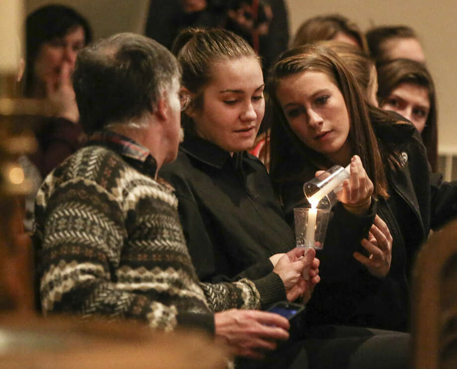 People attend a community prayer vigil at the Emmanuel Evangelical Lutheran Church in Souderton, Pa. for the shooting victims of Bradley W. Stone, in Montgomery County, Pa., Tuesday, Dec. 16, 2014. An Iraq War veteran suspected of killing his ex-wife and five of her relatives was found dead of self-inflicted stab wounds Tuesday in the woods of suburban Philadelphia, ending a day-and-a-half manhunt that closed schools and left people on edge. (AP Photo/The Philadelphia Daily News, Steven M. Falk) THE EVENING BULLETIN, TV OUT, MAGS OUT, NO SALES