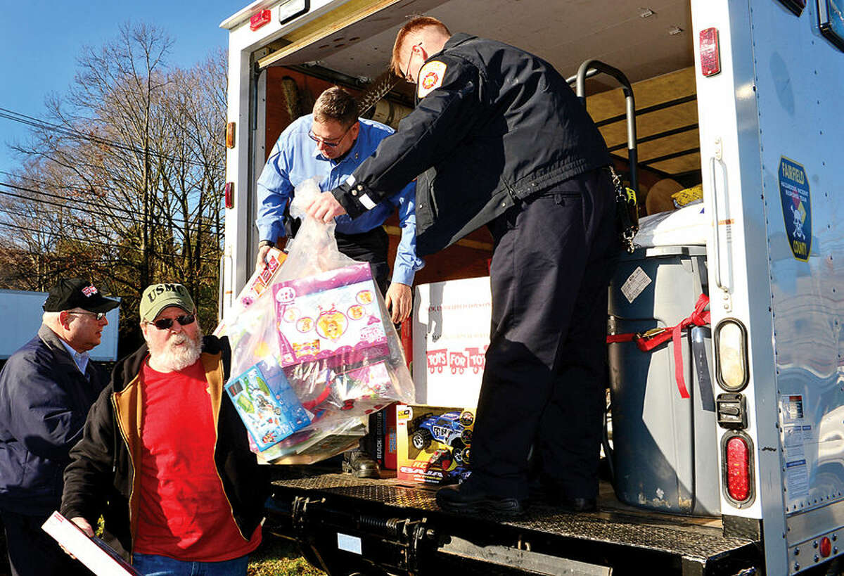 Hour photo / Erik Trautmann Wilton firefighters unload donations to Peter Havens and of Toys for Tots during their annul pick up of toys from Devon Chevy/Buick of Wilton Wednesday morning.