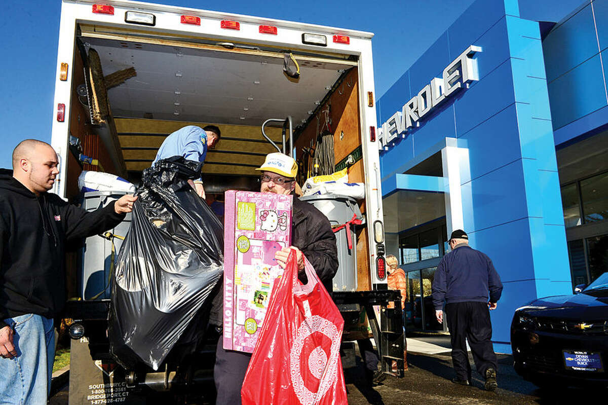 Hour photo / Erik Trautmann Wilton firefighters unload donations Chris Ross of Toys for Tots and Dale Nickel of Devon Chevy/Buick of Wilton during their annul pick up of toys from the Devon car dealership Wednesday morning.