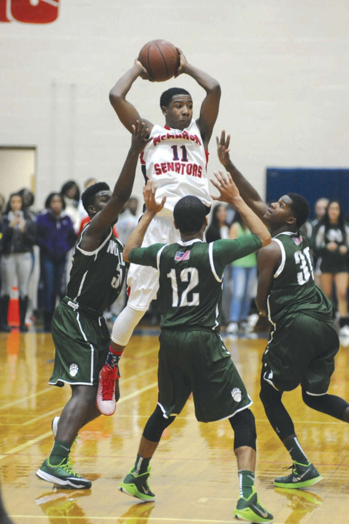 Hour photo/John Nash McMahon's Jahmerikah Green-Younger (11) jumps to make a pass over a trio of Norwalk defenders during Wednesday night's game.