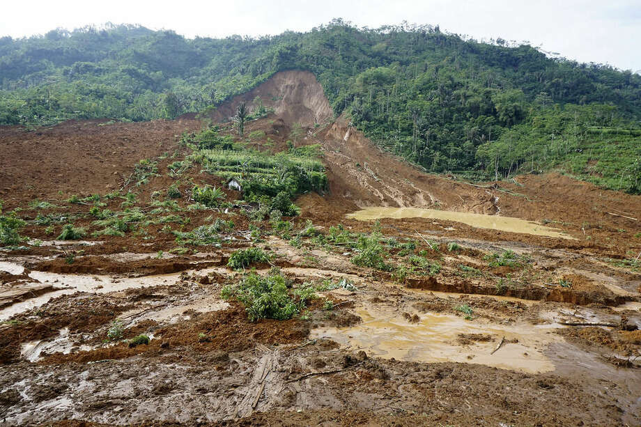 A house, center, is buried in the mud in a village that was swept away by a landslide Jemblung, Central Java, Indonesia, Saturday, Dec. 13, 2014. Torrential rains set off the mudslide down the hills into the village in central Indonesia, killing scores of people with more than 100 missing. (AP Photo/Bayu Nur)