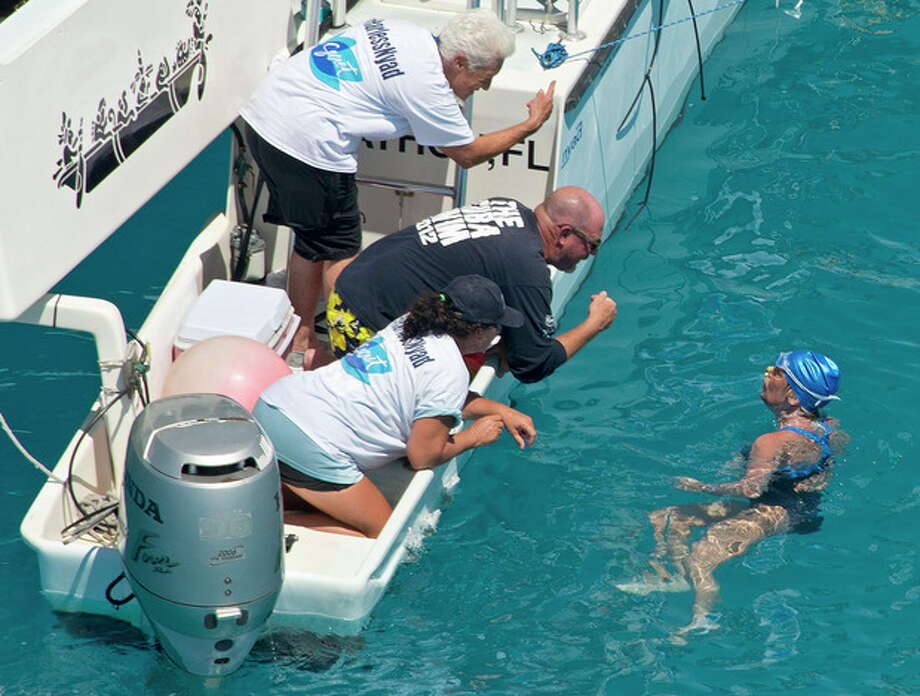 In this photo provided by the Florida Keys News Bureau, swimmer Diana Nyad talks with her crew less than two miles off Key West, Fla., Monday, Sept. 2, 2013. Nyad, 64, is poised to be the first swimmer to cross the Florida Straits from Cuba to the Florida Keys without the security of a shark cage. (AP Photo/Florida Keys News Bureau, Andy Newman) / Florida Keys News Bureau