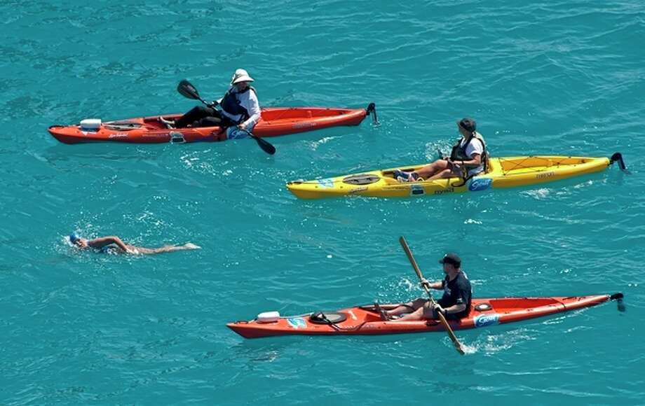 In this photo provided by the Florida Keys News Bureau, Diana Nyad, positioned about two miles off Key West, Fla., Monday, Sept. 2, 2013, is escorted by kayakers as she swims towards the completion of her approximately 110-mile trek from Cuba to the Florida Keys. Nyad, 64, is poised to be the first swimmer to cross the Florida Straits without the security of a shark cage. (AP Photo/Florida Keys News Bureau, Andy Newman) / Florida Keys News Bureau