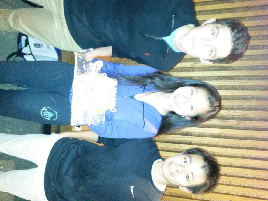 Pictured from left to right areGeorge Mgaloblishvili, Kaitlyn Zheng and Daniel Xie,along with a gingerbread creation.