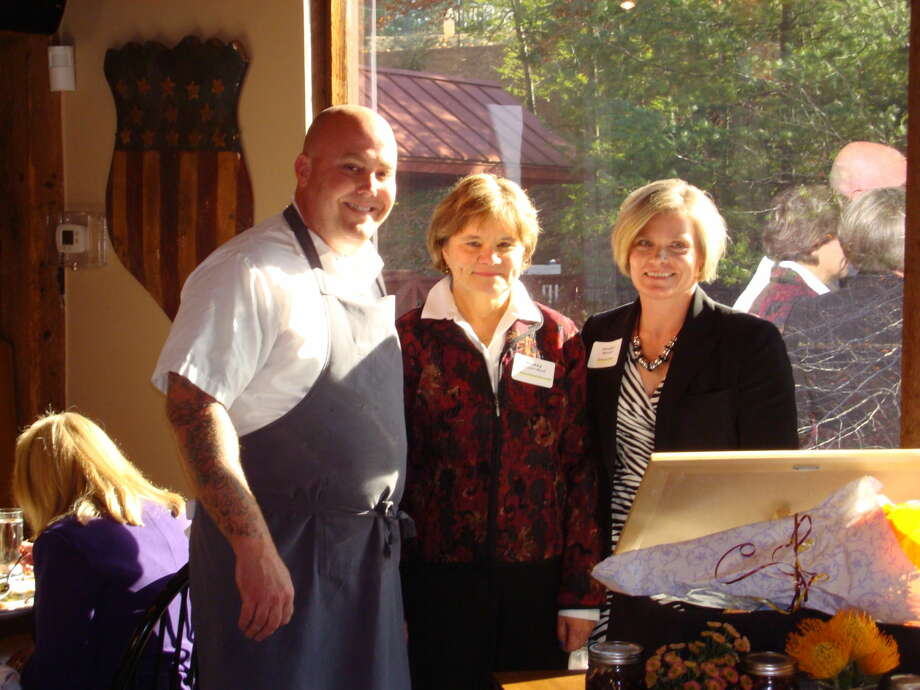 Tyler Anderson, Chef/Owner of Millwright's Restaurant & 1680 Tavern, presents a donation of $1,000 to Simsbury Social Services Director Mickey Lecours-Beck at the Ladies Tertulia luncheon that he recently hosted at his restaurant. Joining them is Jocelyn Mitchell, Senior VP of Simsbury Bank, which sponsored the charity event.