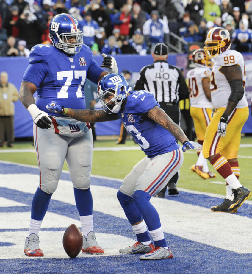 New York Giants wide receiver Odell Beckham Jr. (13) reacts with guard John Jerry (77) after scoring a touchdown against the Washington Redskins during the fourth quarter of an NFL football game, Sunday, Dec. 14, 2014, in East Rutherford, N.J. (AP Photo/Bill Kostroun)