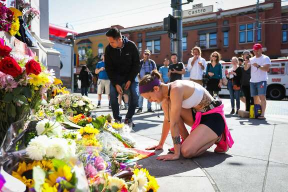 Eden Wetherell, of Orlando, gets emotional as she kneels down next to a memorial in the Castro to honor the fallen victims of the massacre that occurred in an Orlando nightclub, in San Francisco, California, on Sunday, June 12, 2016.