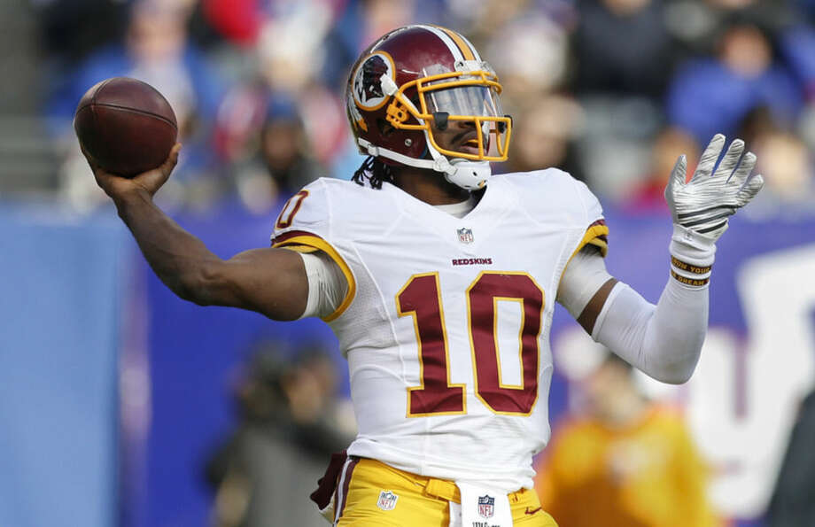 Washington Redskins quarterback Robert Griffin III (10) passes against the New York Giants during the second quarter of an NFL football game, Sunday, Dec. 14, 2014, in East Rutherford, N.J. (AP Photo/Julio Cortez)